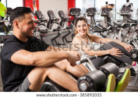 Portrait of a pretty brunette laughing and having fun with his boyfriend while working out together in a gym - stock photo