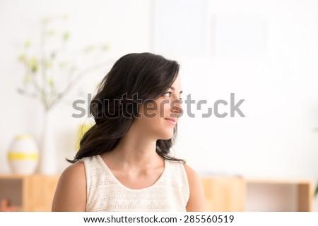 Portrait of a pretty brunette woman looking away - stock photo