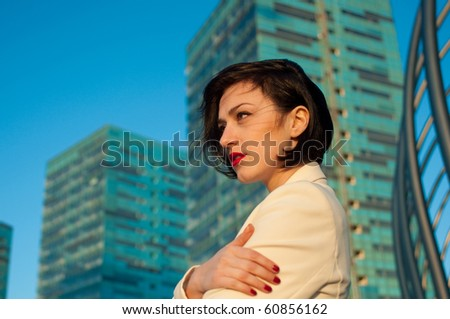 Portrait of a pretty business woman against architecture background - stock photo