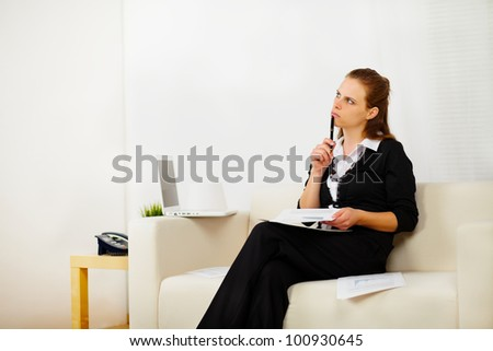 Portrait of a pretty business woman working at home and looking up while she is thinking - stock photo