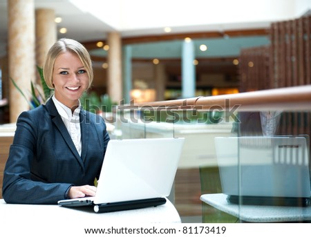 Portrait of a pretty businesswoman sitting at cafe with a laptop using wireless internet, looking happy - stock photo