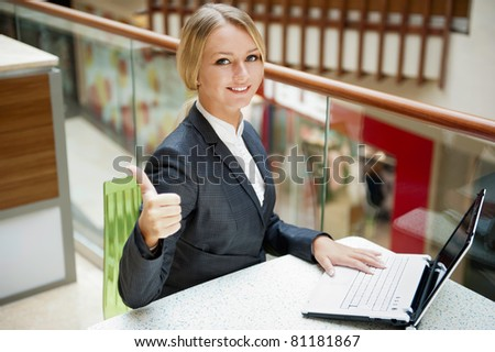 Portrait of a pretty businesswoman sitting at cafe with a laptop using wireless internet, thumbs up - stock photo