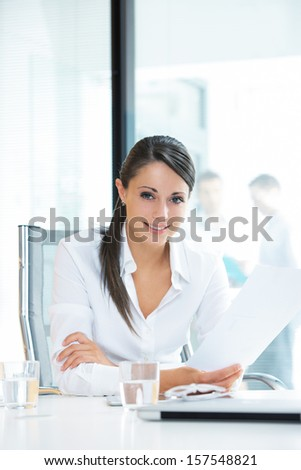 Portrait of a pretty businesswoman smiling, blurred colleagues in the background