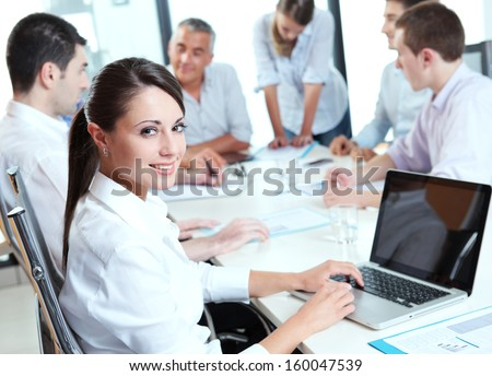 Portrait of a pretty businesswoman smiling during a meeting - stock photo