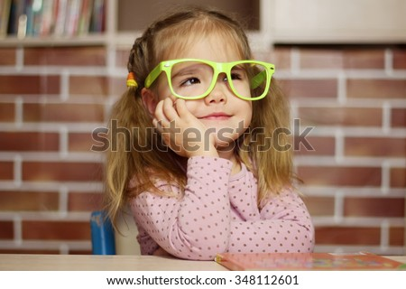 Portrait of a pretty child girl in funny green eyeglasses sitting at the desk with a book, indoor education concept - stock photo