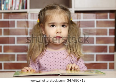Portrait of a pretty child girl sitting at the desk with a book, education concept - stock photo