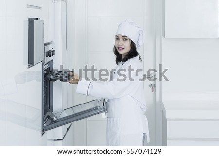 Portrait of a pretty female baker smiling at the camera while putting a baking tray into oven in the kitchen