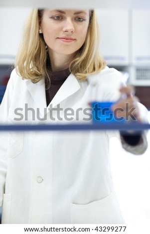 Portrait of a pretty female researcher grabbing a beaker while carrying out experiments in a lab