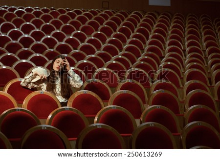 portrait of a pretty girl in a movie theater wearing hat, dreaming elegant - stock photo