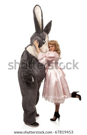 portrait of a pretty girl in pink dress with a big grey fur's color rabbit against white background - stock photo