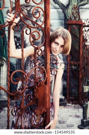 portrait of a pretty girl in the rusty gate at the old cemetery - stock photo
