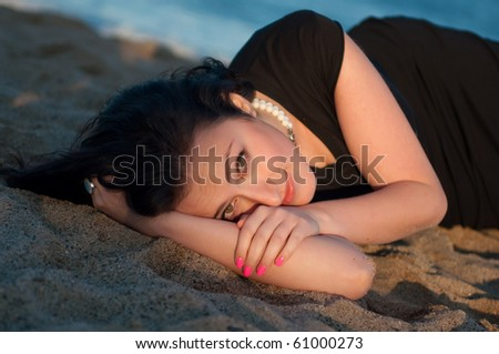 Portrait of a pretty girl resting on the sand - stock photo