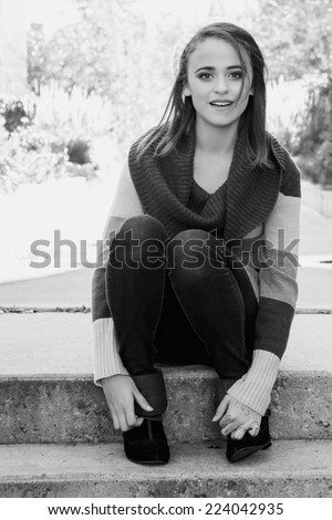 Portrait of a pretty girl sitting on concrete stairs in black and white - stock photo
