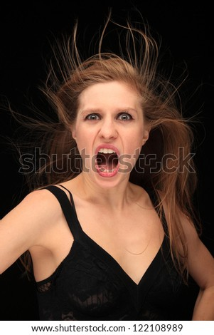 portrait of a pretty girl with blown hair and expression on a black background