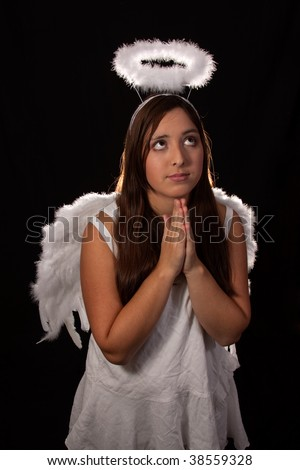 Portrait of a pretty hispanic teen age girl with long brown and eyes wearing a white angel costume with wings and halo praying - stock photo