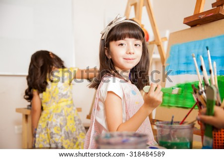 Portrait of a pretty little artist holding a brush and smiling while working on a painting for art class - stock photo
