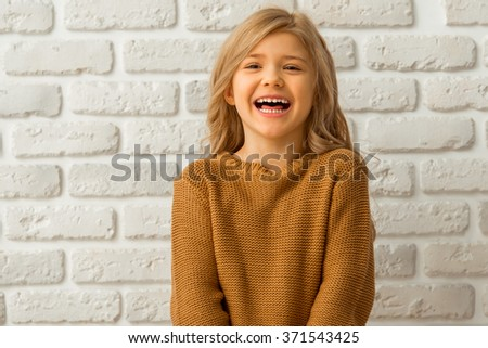 Portrait of a pretty little blonde girl looking in camera and laughing while standing against white brick wall - stock photo