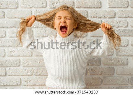 Portrait of a pretty little blonde girl showing emotions, screaming and pulling her hair while standing against white brick wall - stock photo