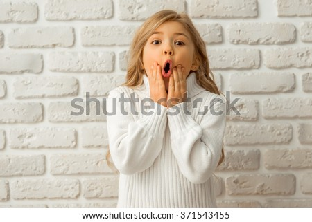 Portrait of a pretty little blonde girl showing emotions while standing against white brick wall - stock photo