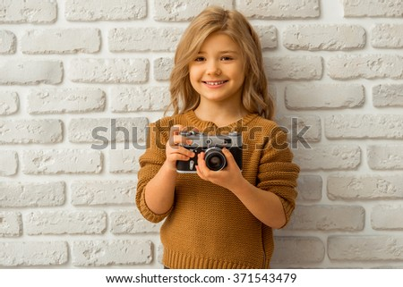 Portrait of a pretty little blonde girl smiling and holding a camera while standing against white brick wall - stock photo