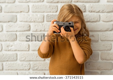 Portrait of a pretty little blonde girl smiling and making a photo while standing against white brick wall - stock photo