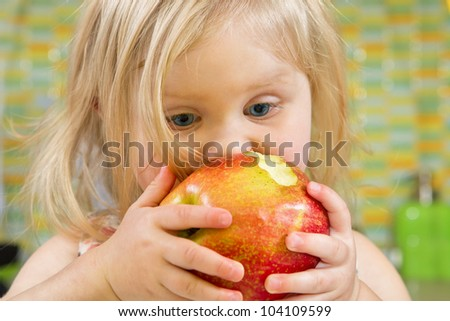Portrait of a pretty little girl biting a red apple - stock photo