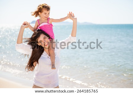 Portrait of a pretty little girl piggyback riding her mother while spending the day in the beach - stock photo