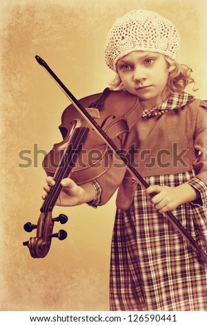 Portrait of a pretty little girl posing with her violin. Vintage style. - stock photo