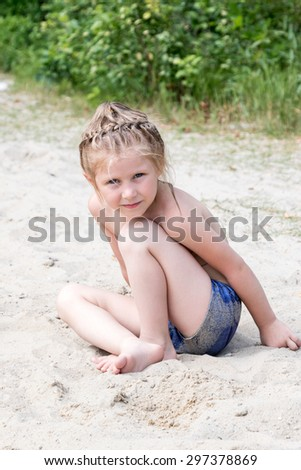 Portrait of a pretty little girl sitting in the sand on the beach - stock photo