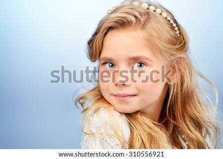 Portrait of a pretty little girl with beautiful blonde hair looking to camera and smiling. Kids fashion. Cosmetics, accessories.  - stock photo
