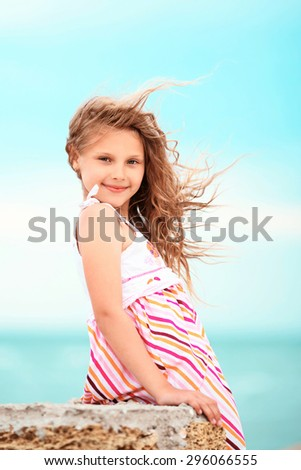 Portrait of a pretty little girl with waving in the wind long hair sitting on the beach against the blue sky - stock photo