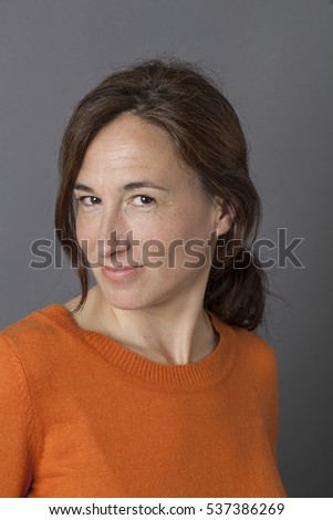 portrait of a pretty middle aged woman with long brown hair for sexy beauty and natural seduction, grey background studio