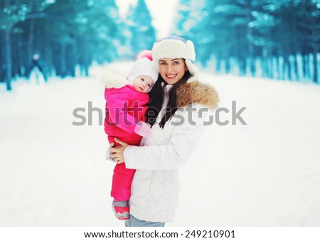 Portrait of a pretty mother and baby in the winter day