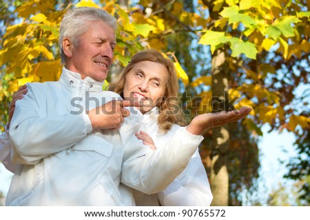 portrait of a pretty old couple at autumn park