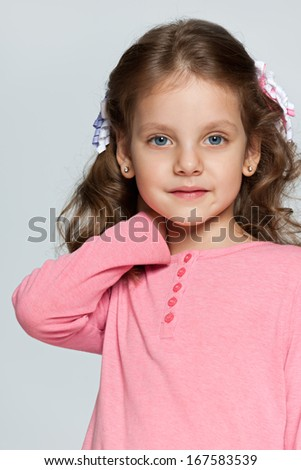 Portrait of a pretty pensive small girl on the grey background