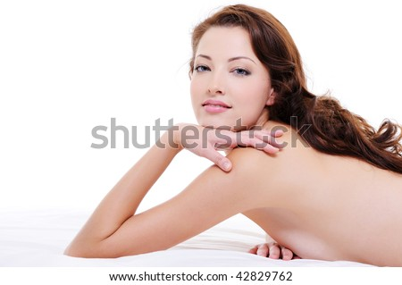 Portrait of a  pretty red hair woman with nude body lying on white bed - stock photo