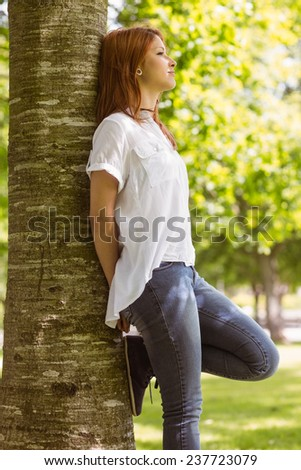 Portrait of a pretty redhead leaning against trunk in park - stock photo