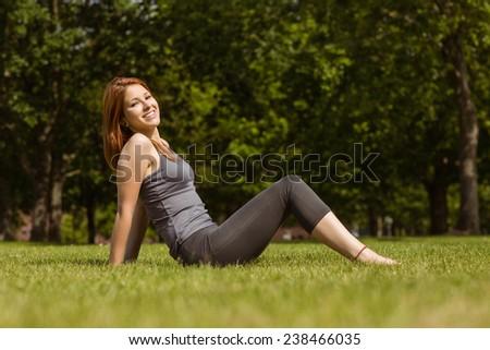Portrait of a pretty redhead sitting carefree in sunshine - stock photo