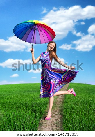 Portrait of a pretty smiling woman with colorful umbrella - stock photo
