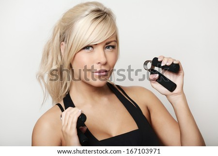 portrait of a pretty sporty woman shot in the studio using hand grip strengthener