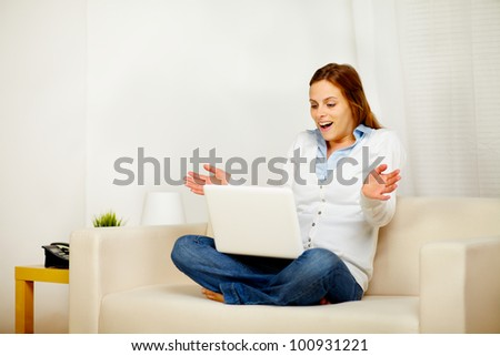 Portrait of a pretty surprised girl working on sofa