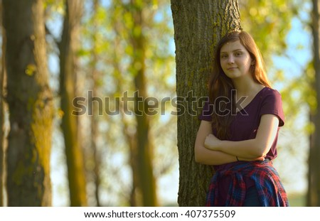 Portrait of a Pretty Teen Girl Standing in a Forest - stock photo