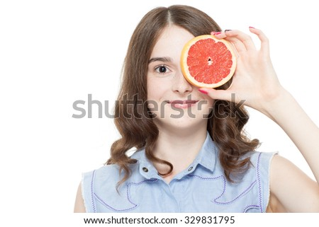 Portrait of a pretty teenage brunette girl posing holding a piece of a grapefruit in front of her eye, isolated on white background smiling  - stock photo