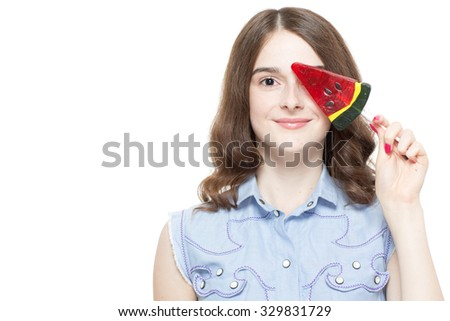 Portrait of a pretty teenage brunette girl posing with a watermelon lollipop smiling, isolated on white background - stock photo