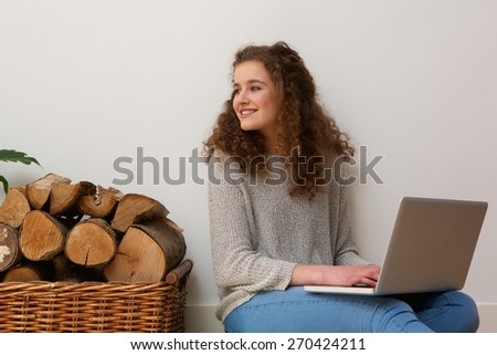 Portrait of a pretty teenage girl smiling with laptop at home - stock photo