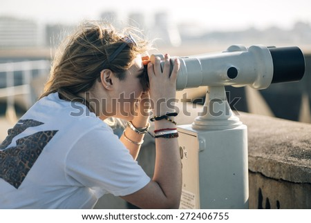 Portrait of a pretty teenage girl with a tourist telescope