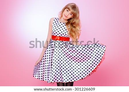 Portrait of a pretty teenager girl posing in pin-up dress over pink background. Beauty, fashion. - stock photo