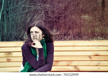 portrait of a pretty thoughtful lady sitting on a banch in a park with artistic colors and shadows added - stock photo