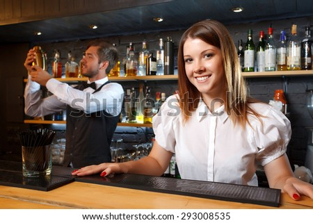 Portrait of a pretty waitress standing at the counter smiling and looking at the camera while a handsome bartender holding a glass and wiping it, shelves full of bottles with alcohol on the background