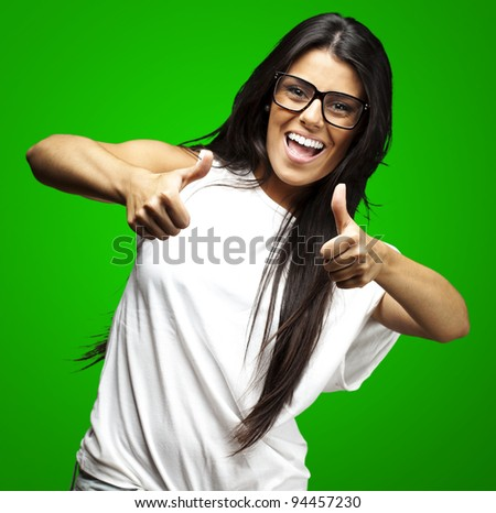 portrait of a pretty woman doing approve symbol over green background - stock photo